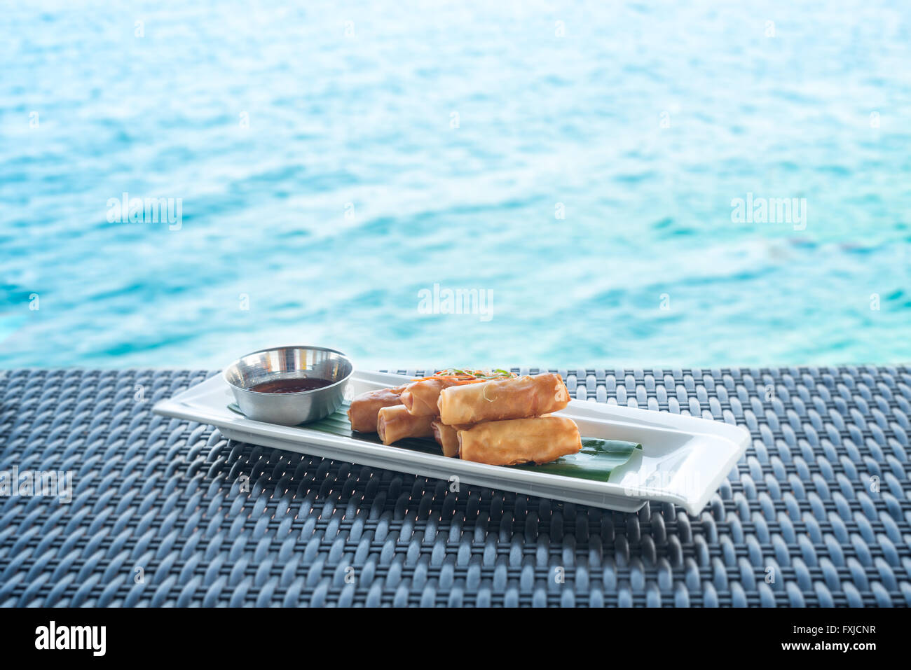 Vegetable fried spring rolls served with bittersweet sauce on wicker table and water background - Stock Image