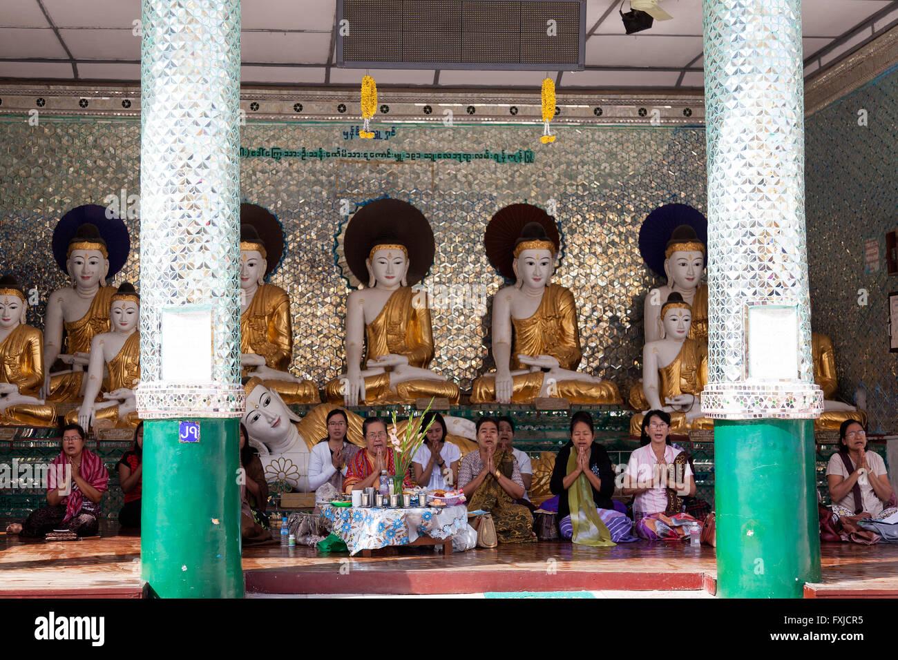 Cross-legged worshippers praying and singing in an annex of the Paya Shwedagon, in Yangon (Myanmar). Croyantes assises Stock Photo