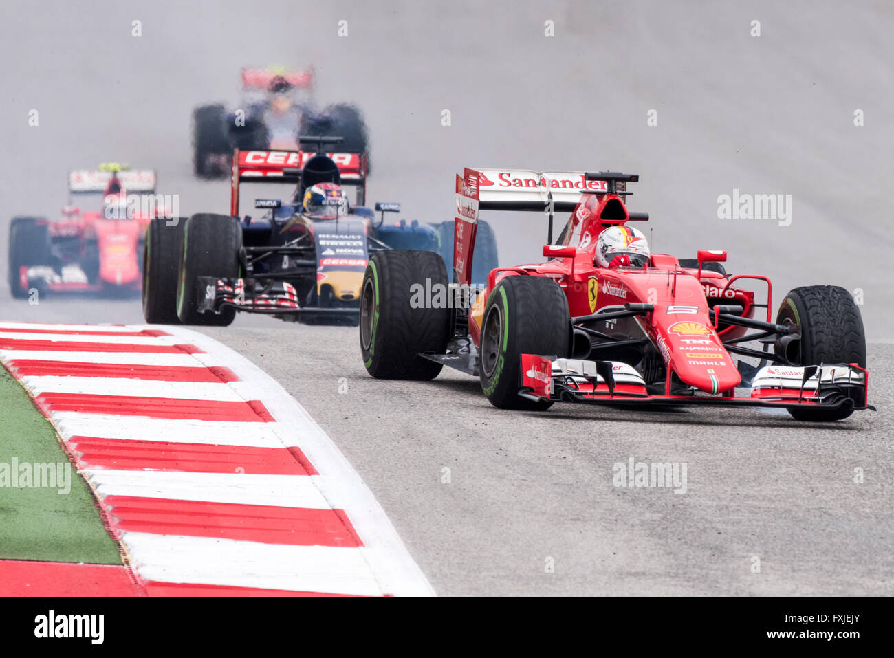 Sebastian Vettel's Ferrari leads a group of cars into turn 11 at Circuit of the Americas during the 2015 US Grand Stock Photo
