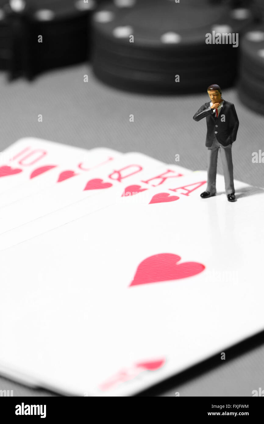 Miniature businessman poker hand chips gambling - Stock Image