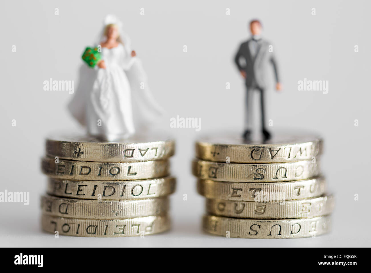 Close up/macro model stock photo depicting married husband and wife on £1 pound coin stack - Stock Image