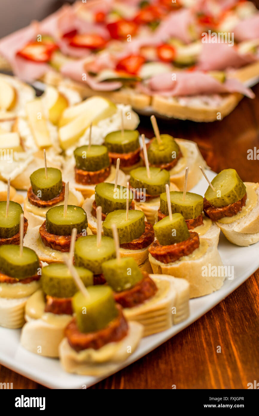 Canapes with sausage and gherkin wood table - Stock Image