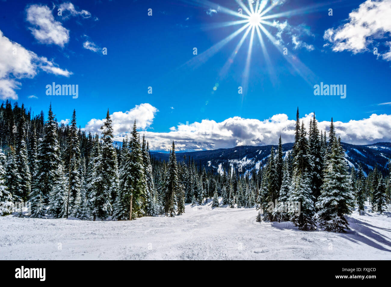 Bright sun and blue sky on the ski hills at Sun Peaks village  in the Shuswap Highlands of British Columbia Stock Photo