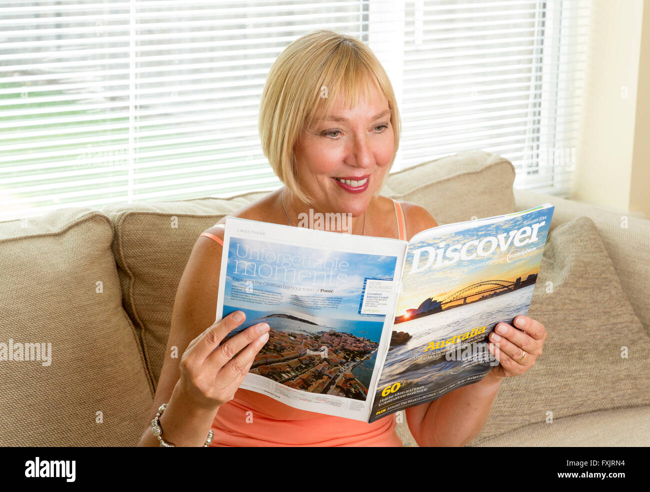 woman reading a travel guide magazine - Stock Image