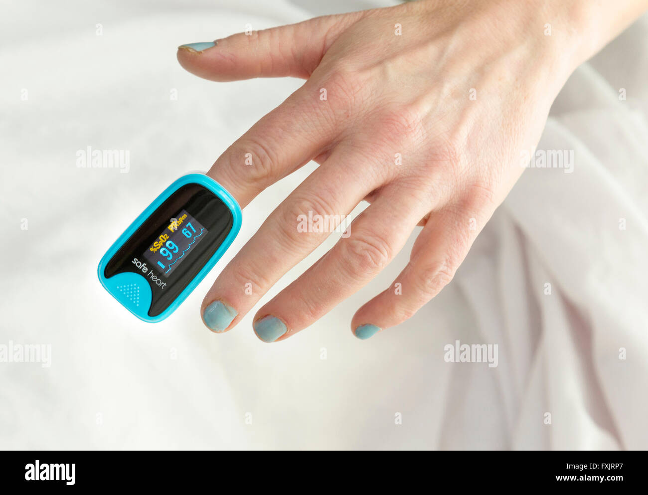 woman using a pulse oximeter - Stock Image
