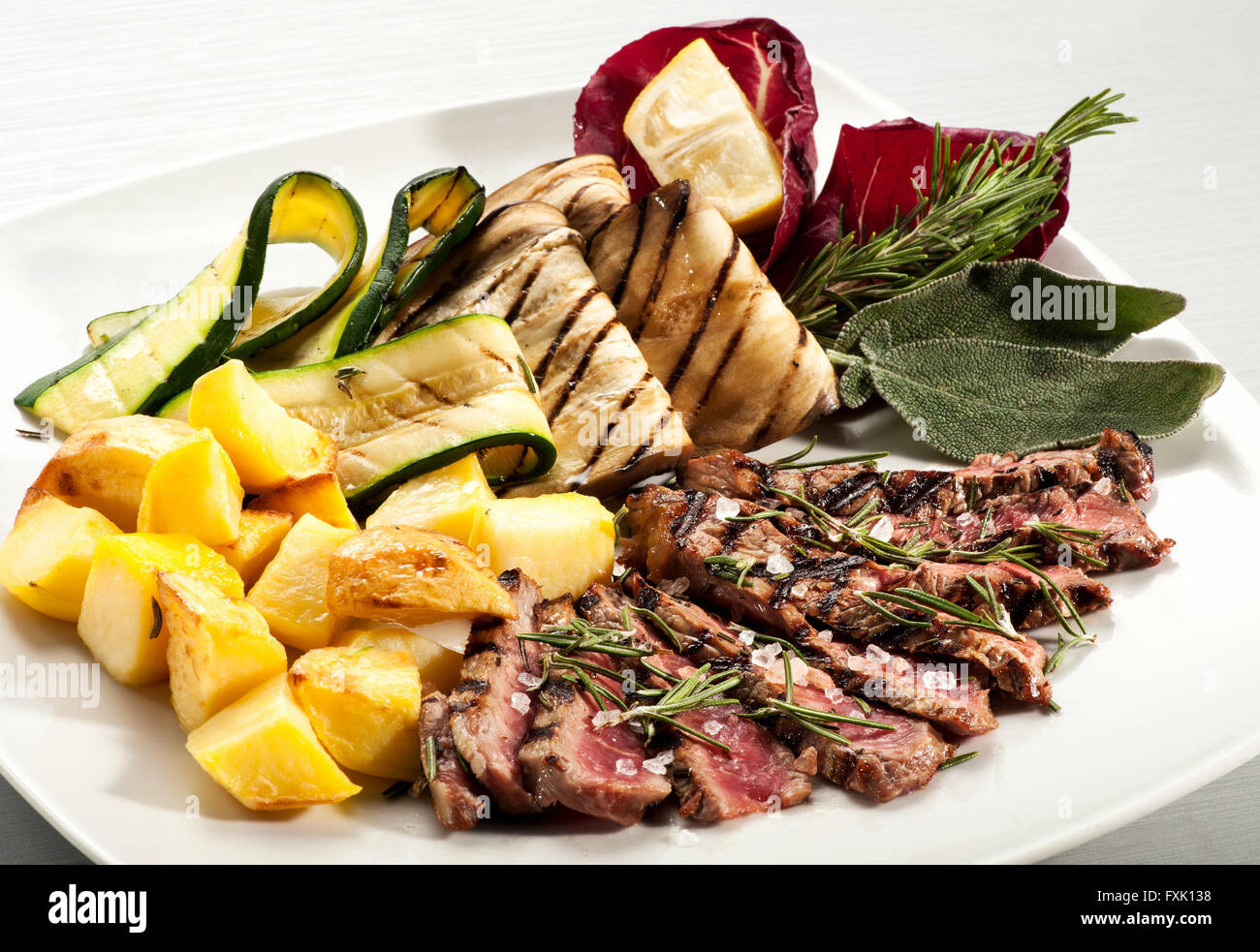 Single serving of rare cooked steak slices, baked yellow potato, eggplant and squash with herbs on plate Stock Photo