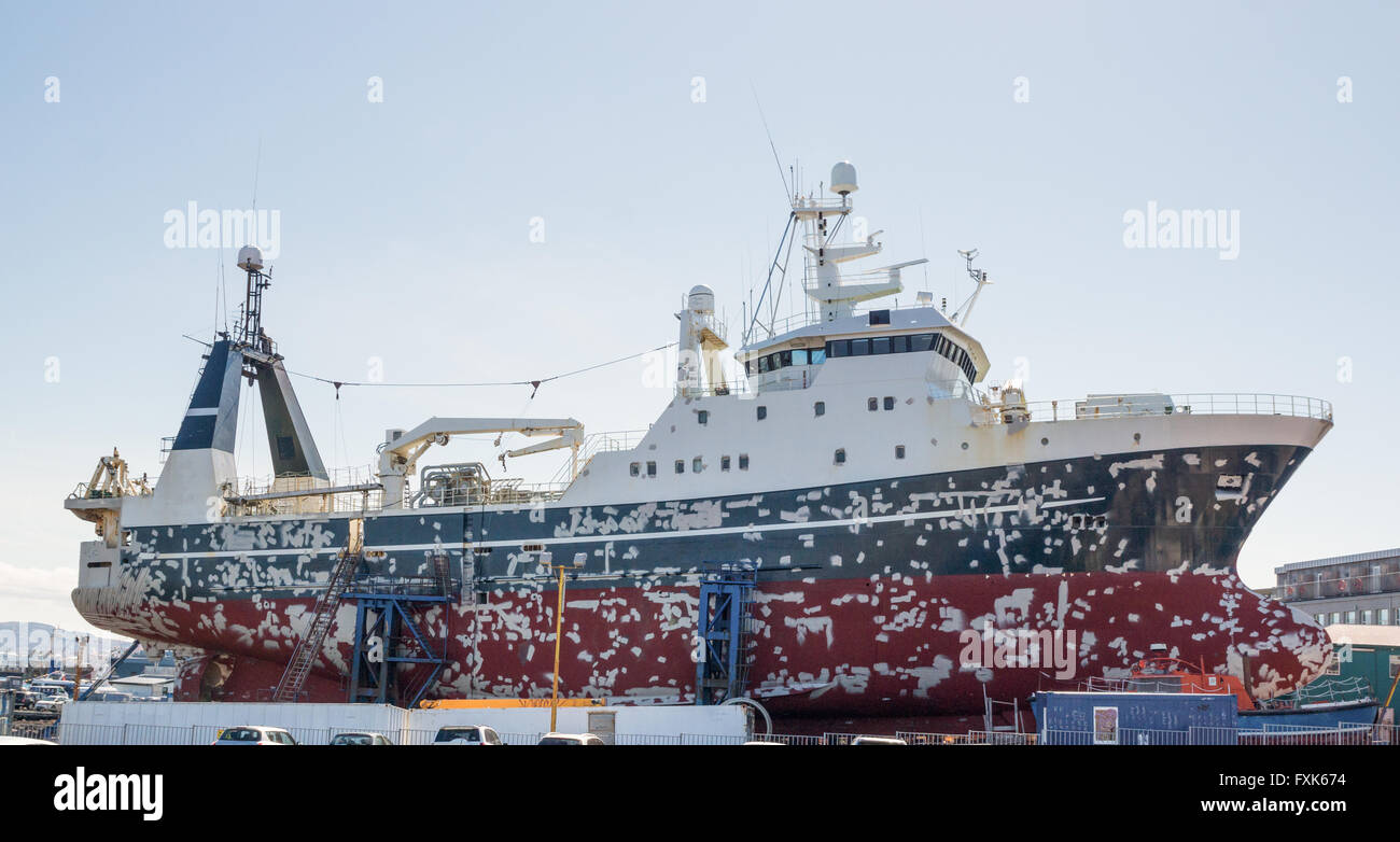Large ship in dry dock preparing for painting and repairs - Stock Image