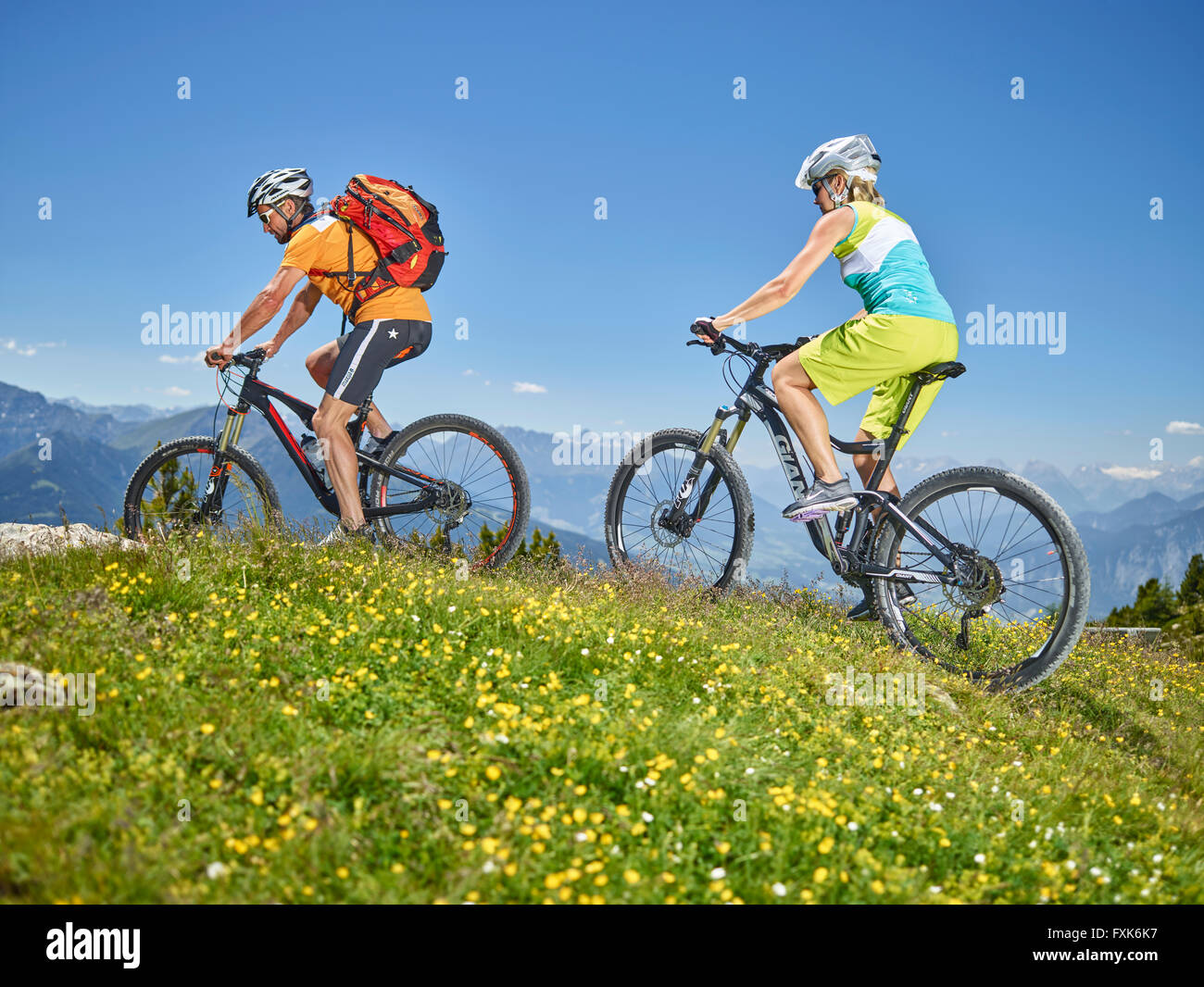 Man 40-45 years and woman 35-40 years with helmets cycle with their mountain bikes, Zirbenweg, Patscherkofel, Innsbruck, - Stock Image