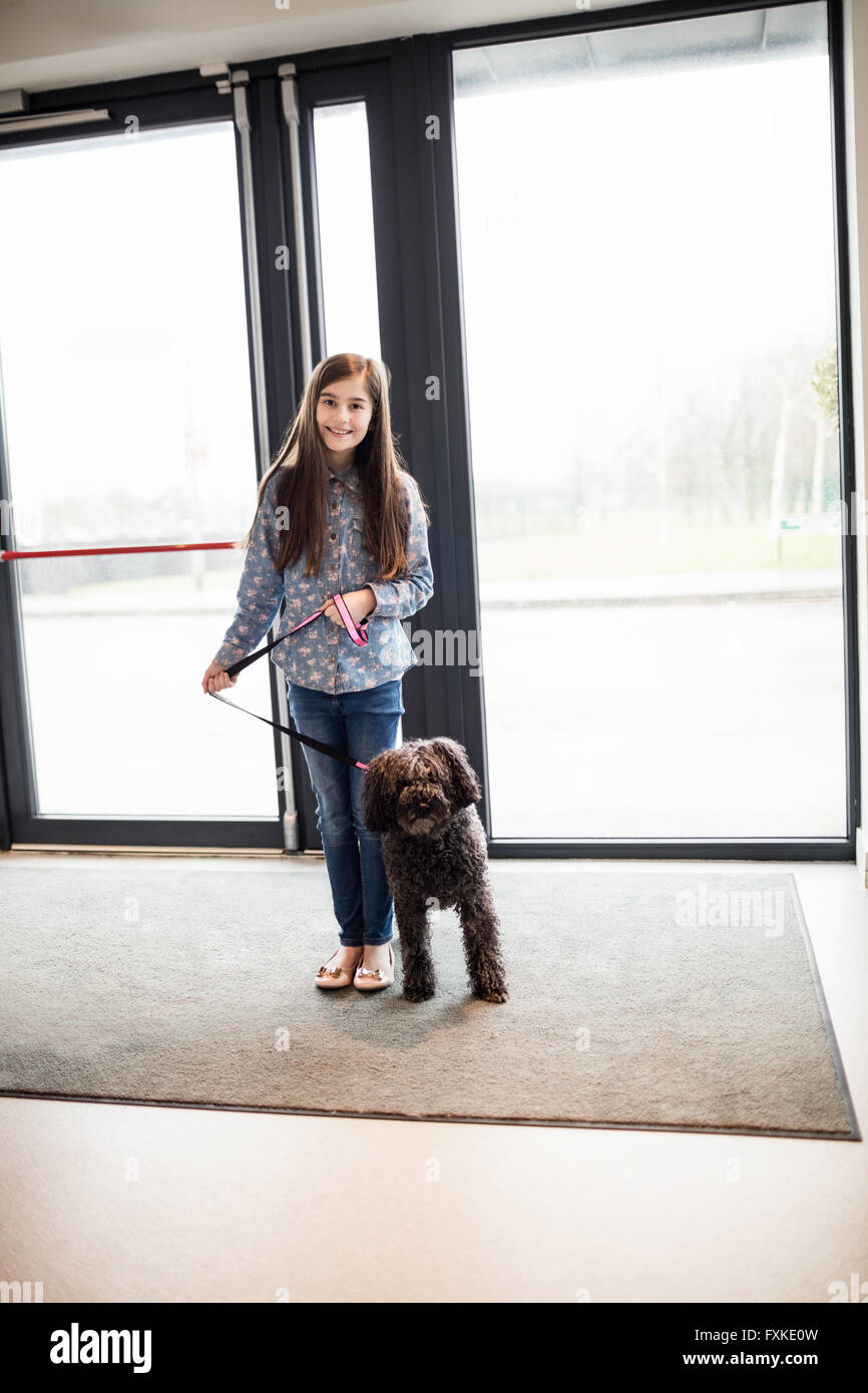 Portrait of girl with dog visiting clinic - Stock Image
