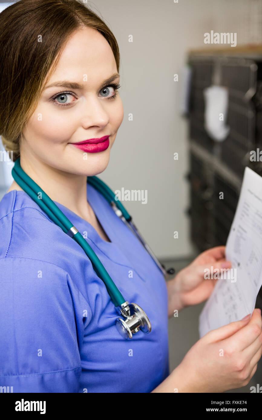 Portrait of vet monitoring sick rabbit in cage Stock Photo