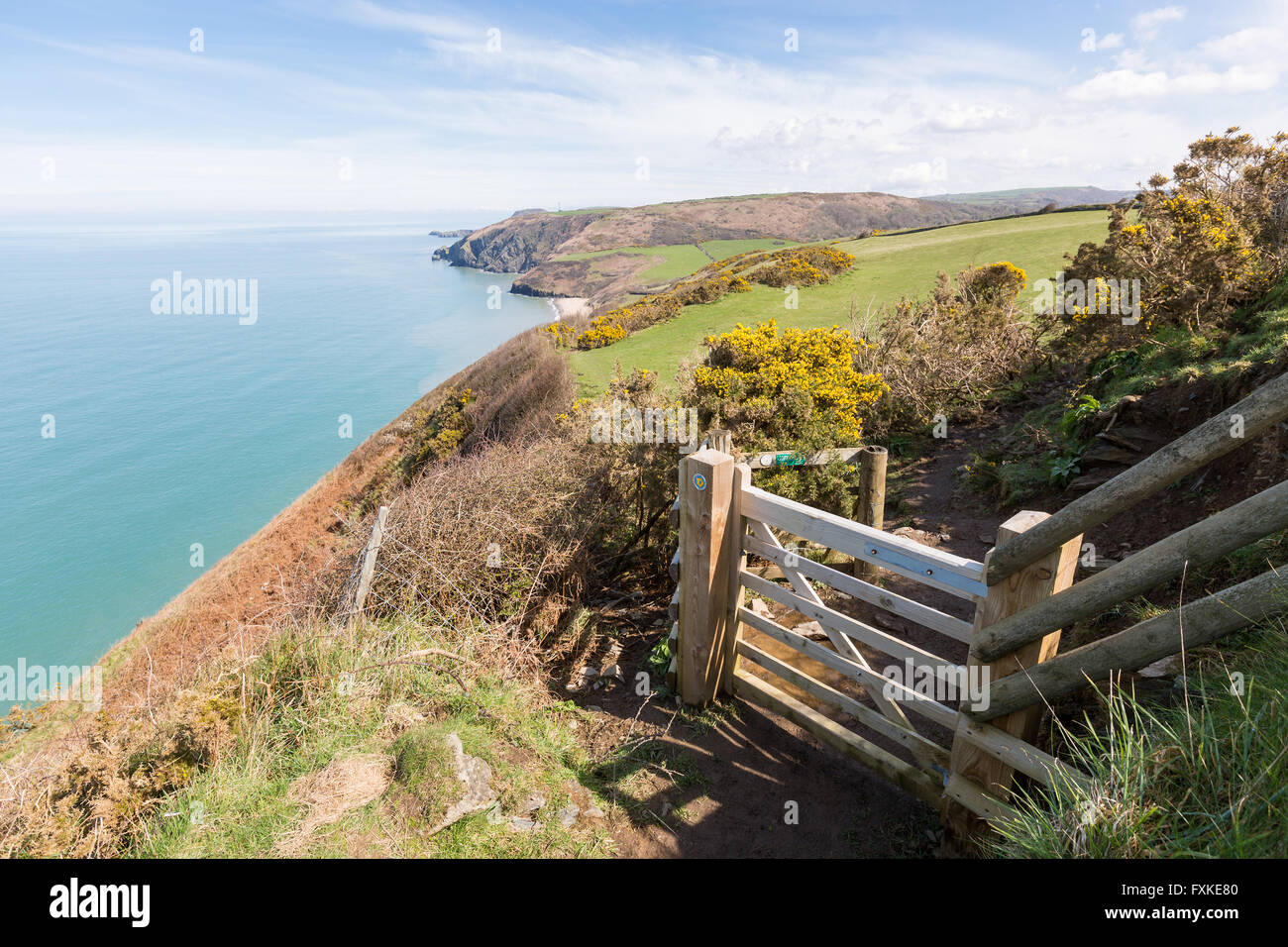 Wooden gate leading onto the Cardigan Bay Coastal Path. Penbryn Beach can be seen in the distance. - Stock Image