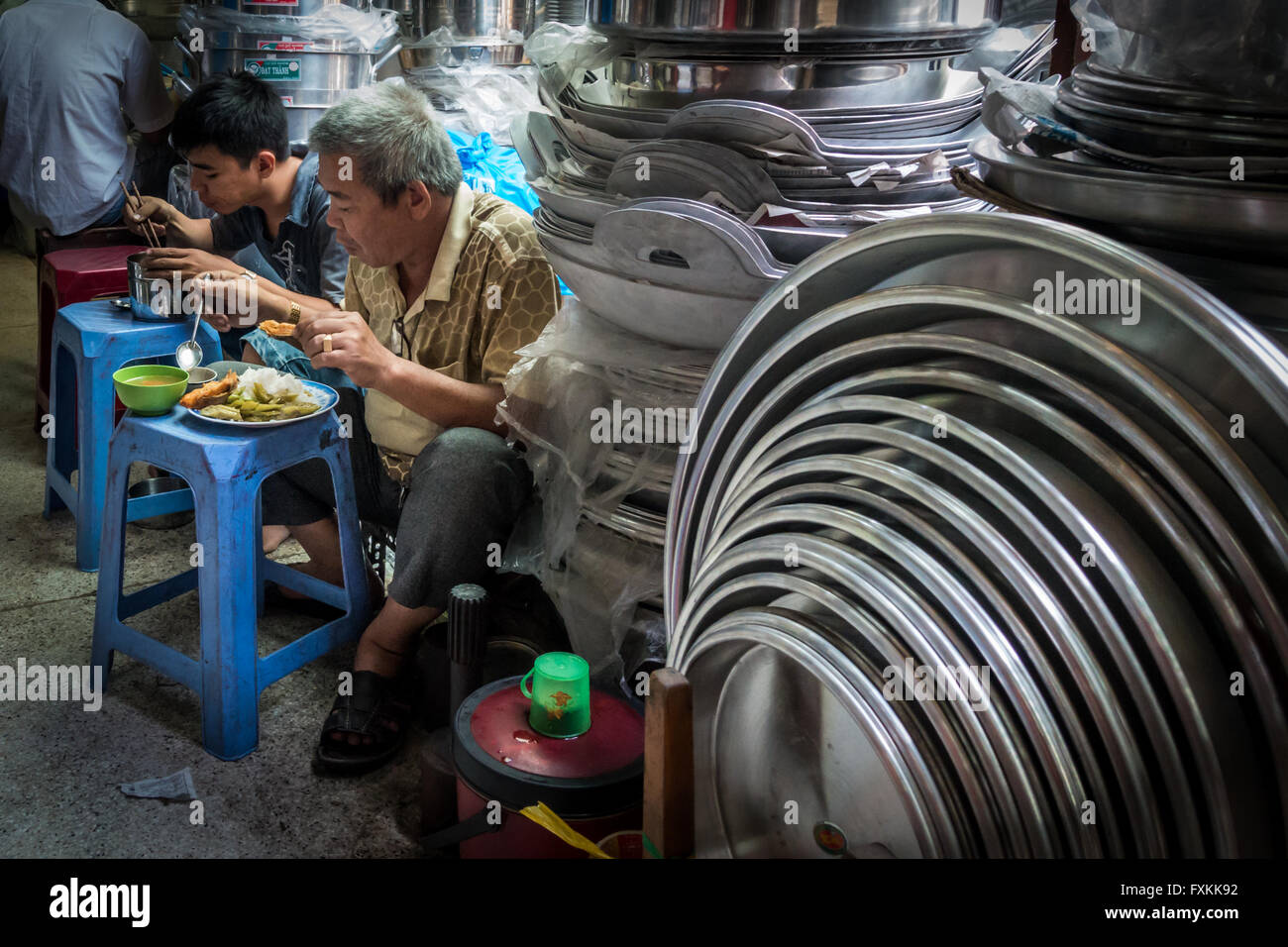 Locals eating lunch inside Binh Tay Market, Ho Chi Minh City, Vietnam - Stock Image