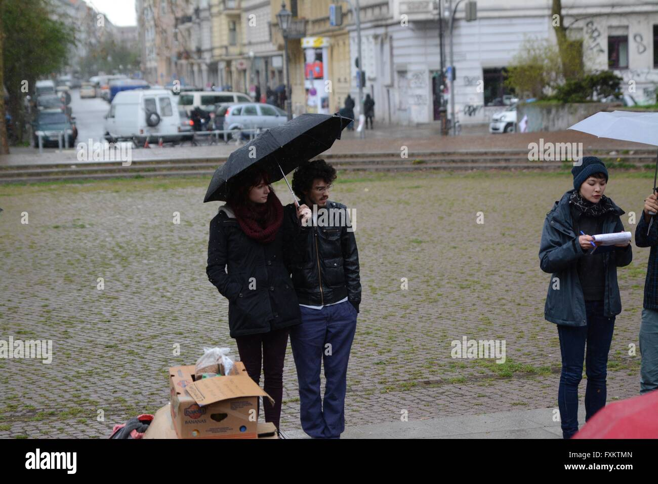 Berlin, Germany. 16th April 2016. Organisers shield themselves from the impending storm as they speak to the gathered - Stock Image