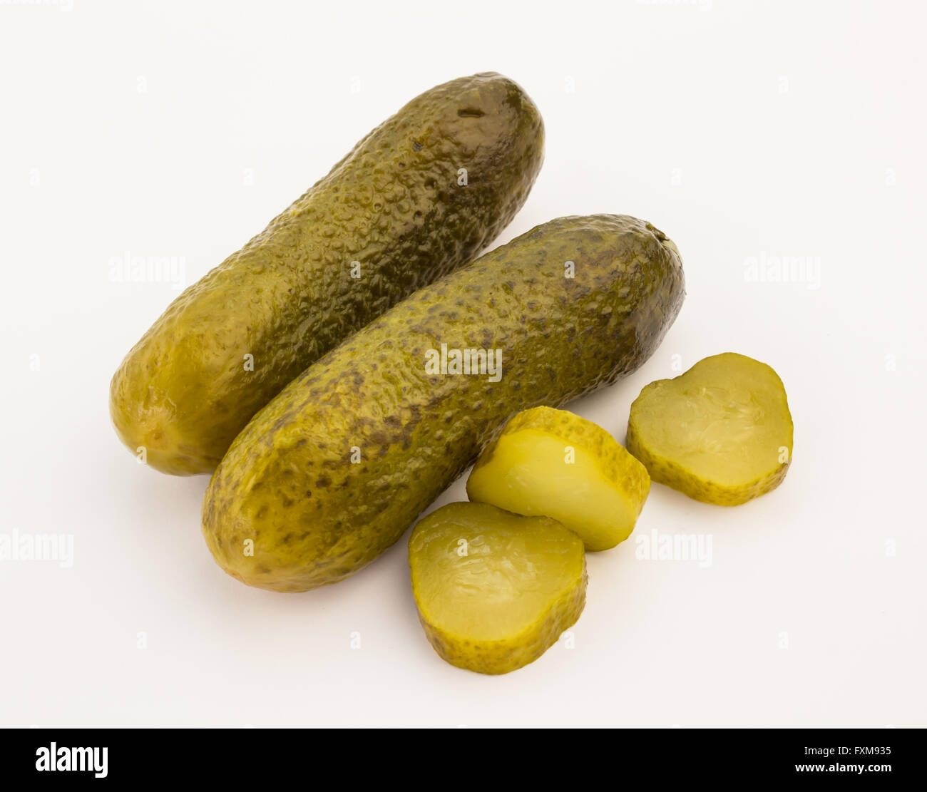 Close up of two pickles and slices isolated on white background - Stock Image