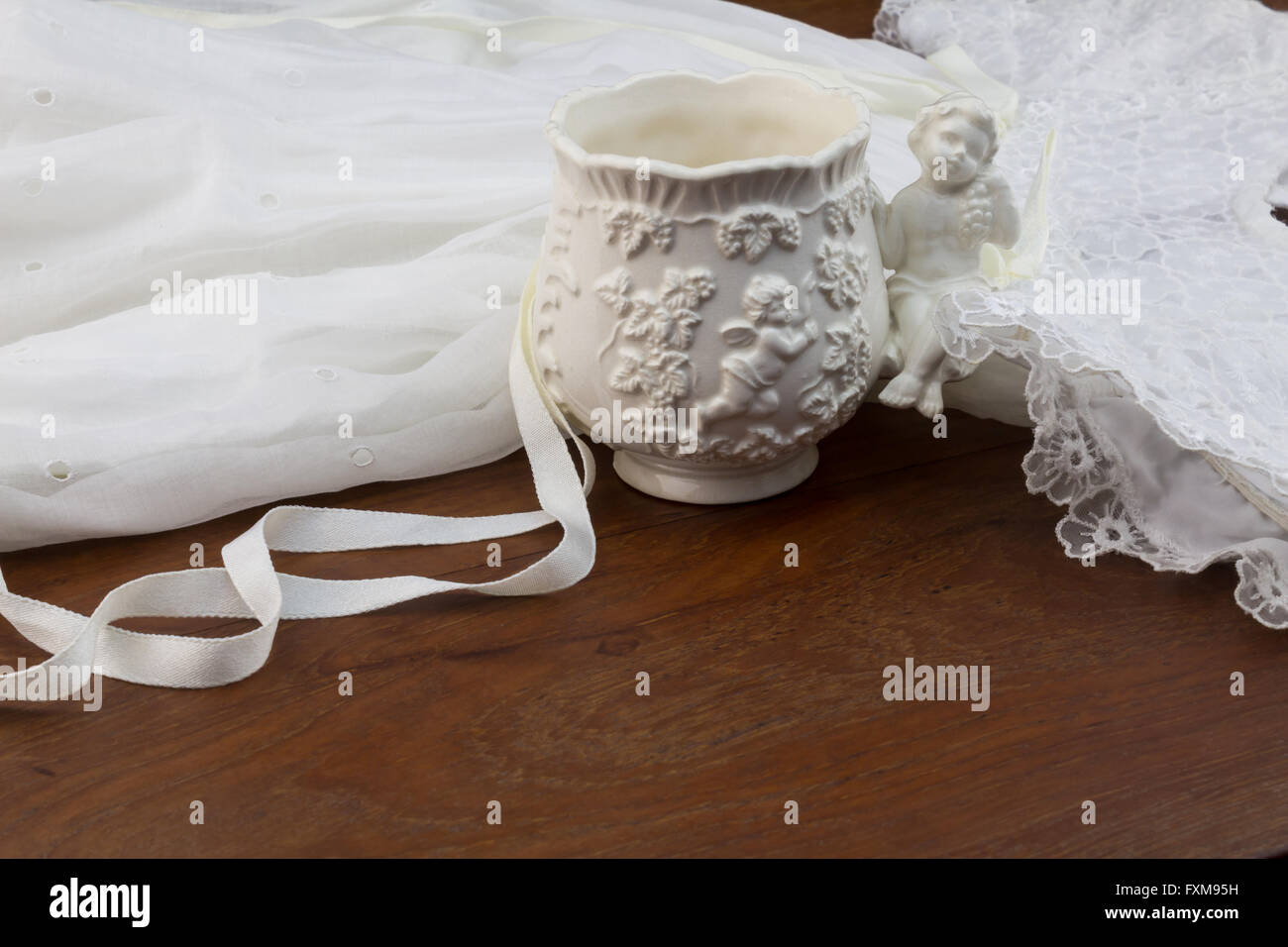 Vintage porcelain baby christening cup and baptism dress on wooden table - Stock Image