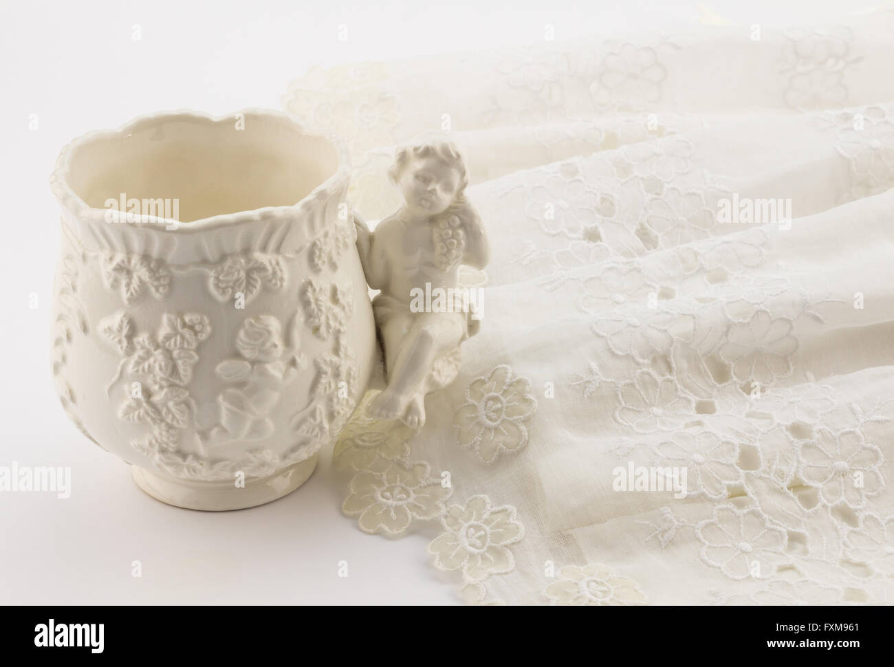 Vintage white baptism cup and baby christening dress isolated on white background - Stock Image