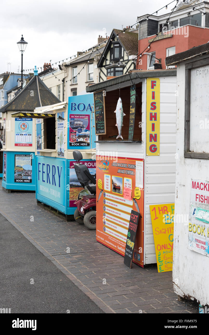 Boat trip and tourist fishing trip sheds and kiosks on the harbour at Brixham Devon UK - Stock Image