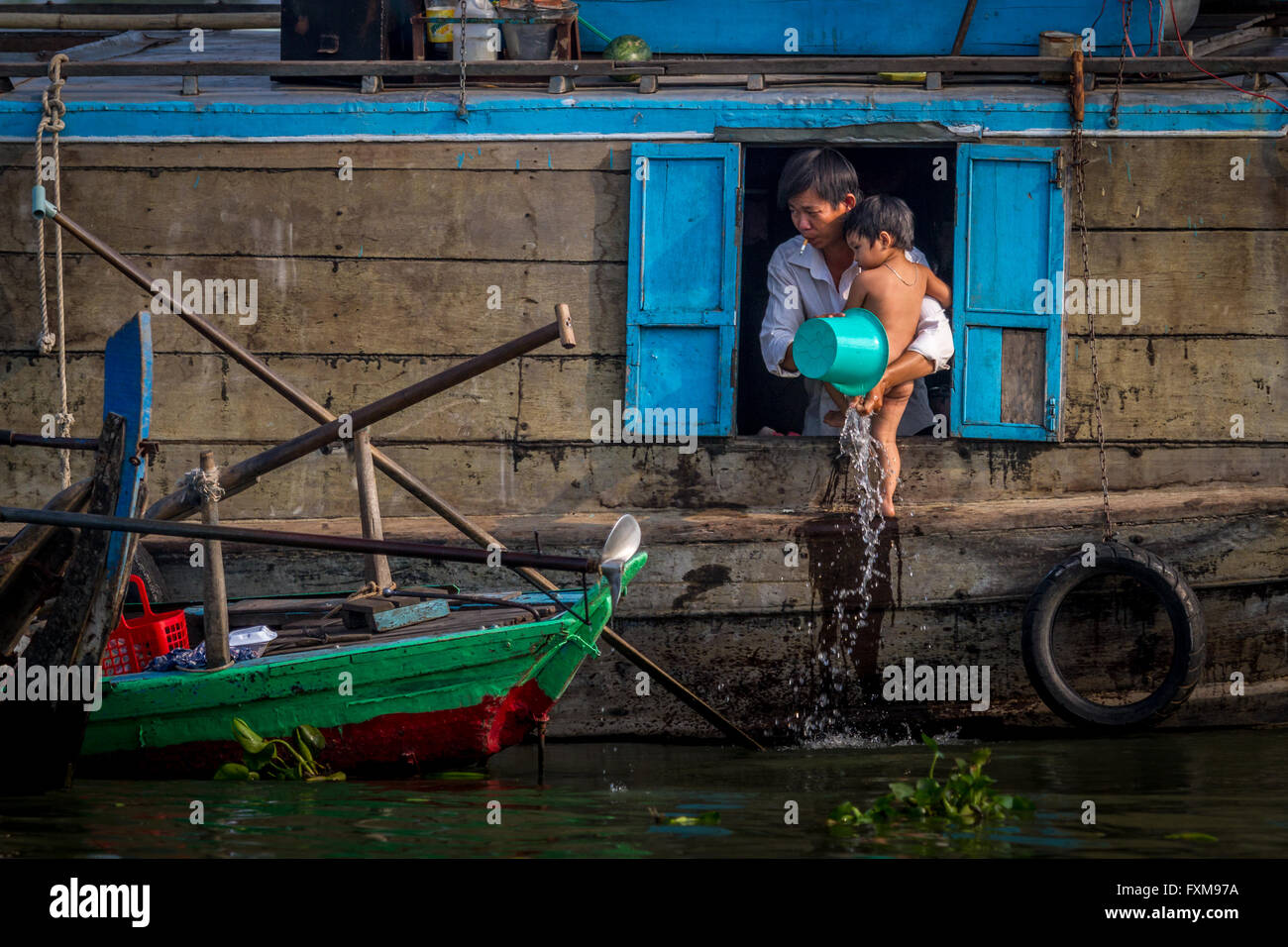 Floating village daily family life - family with child bathing on a house boat; Chau Doc, Mekong Delta, Vietnam - Stock Image