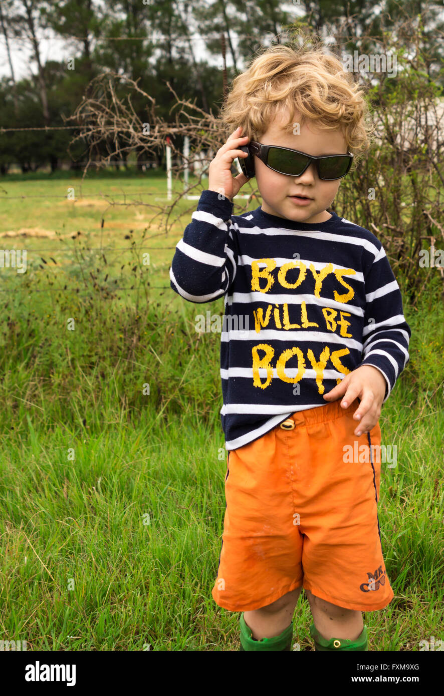 Photo of young boy with sunglasses talking to a camera lens cap pretending it is a mobile phone in a rural setting Stock Photo