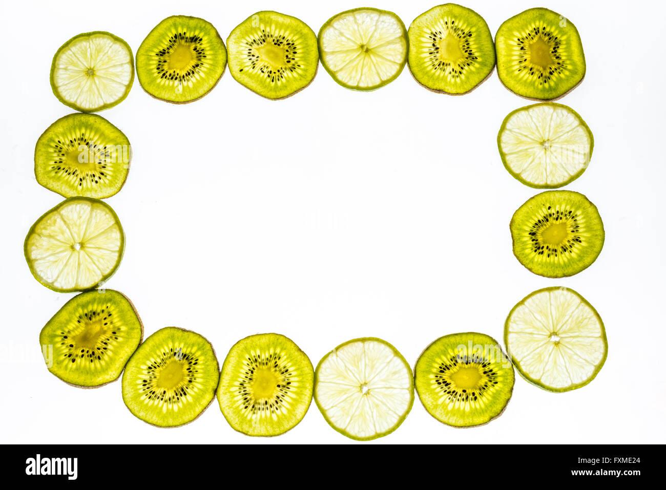 Frame made of fresh kiwi fruit and limes isolated on white background - Stock Image