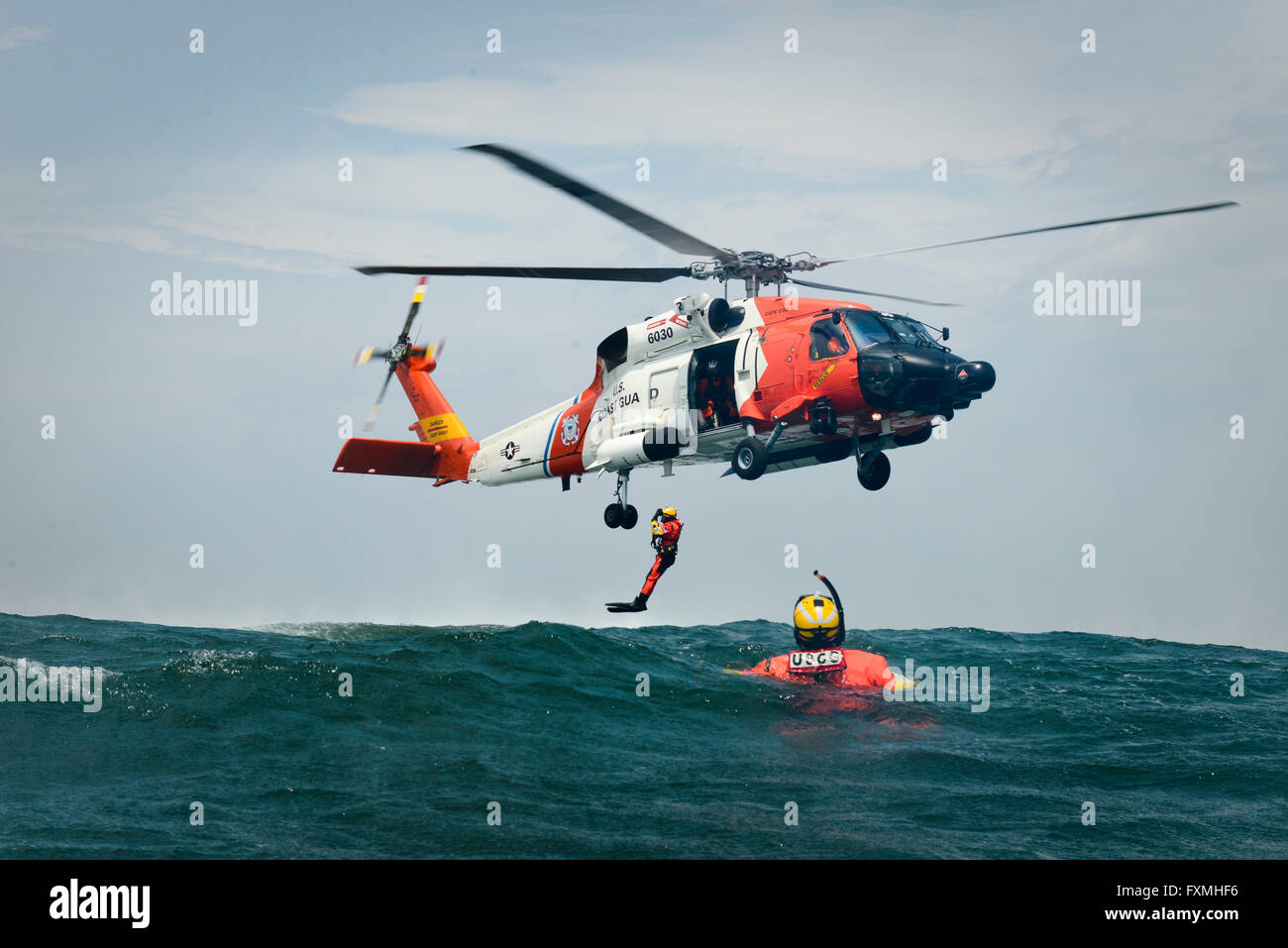 a us coast guard rescue swimmers are deployed from a mh 60 jayhawk helicopter during rescue training in the atlantic ocean june 23 2015 near cape cod