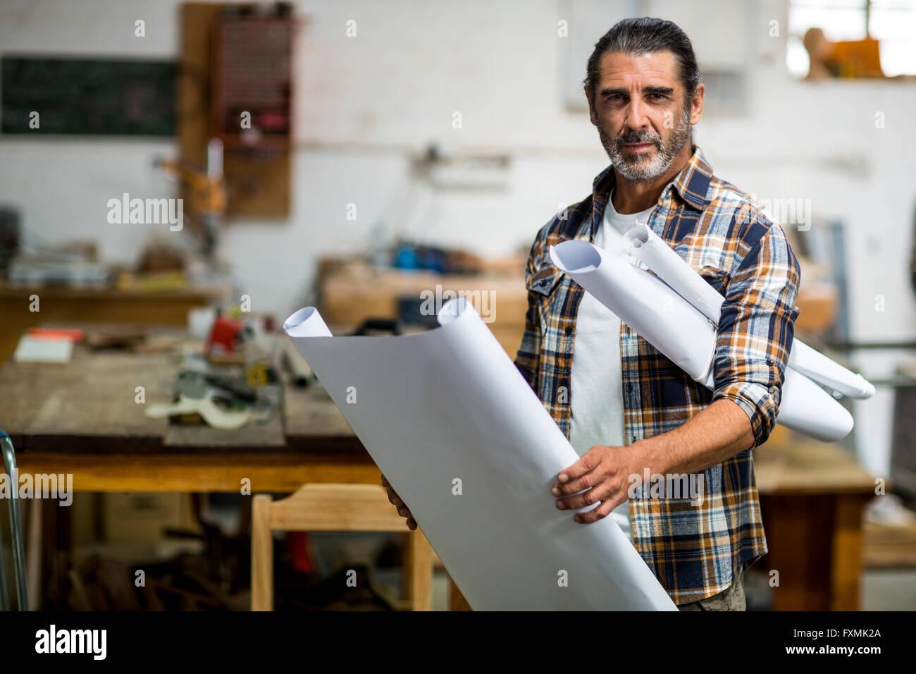 Portrait of carpenter with blueprint - Stock Image