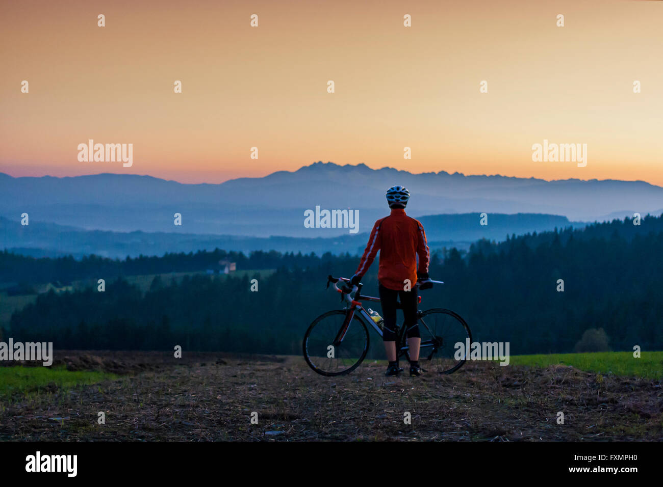 Cyclist looking at the sunset over the Tatra mountains in Poland - Stock Image