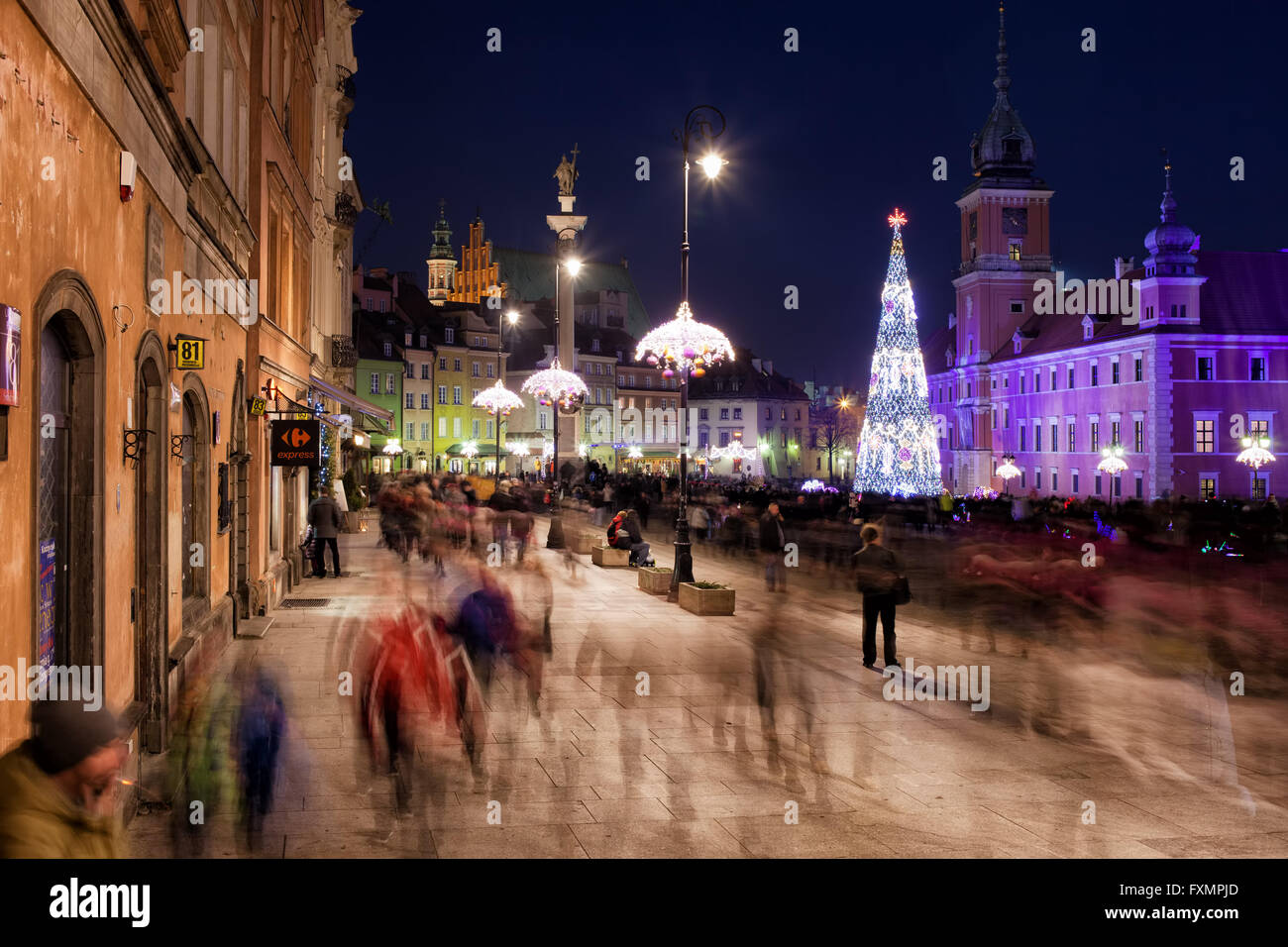 Warsaw by night in Poland, Old Town Square, Royal Castle, people, tourists crowd, city break, city life, Christmas - Stock Image