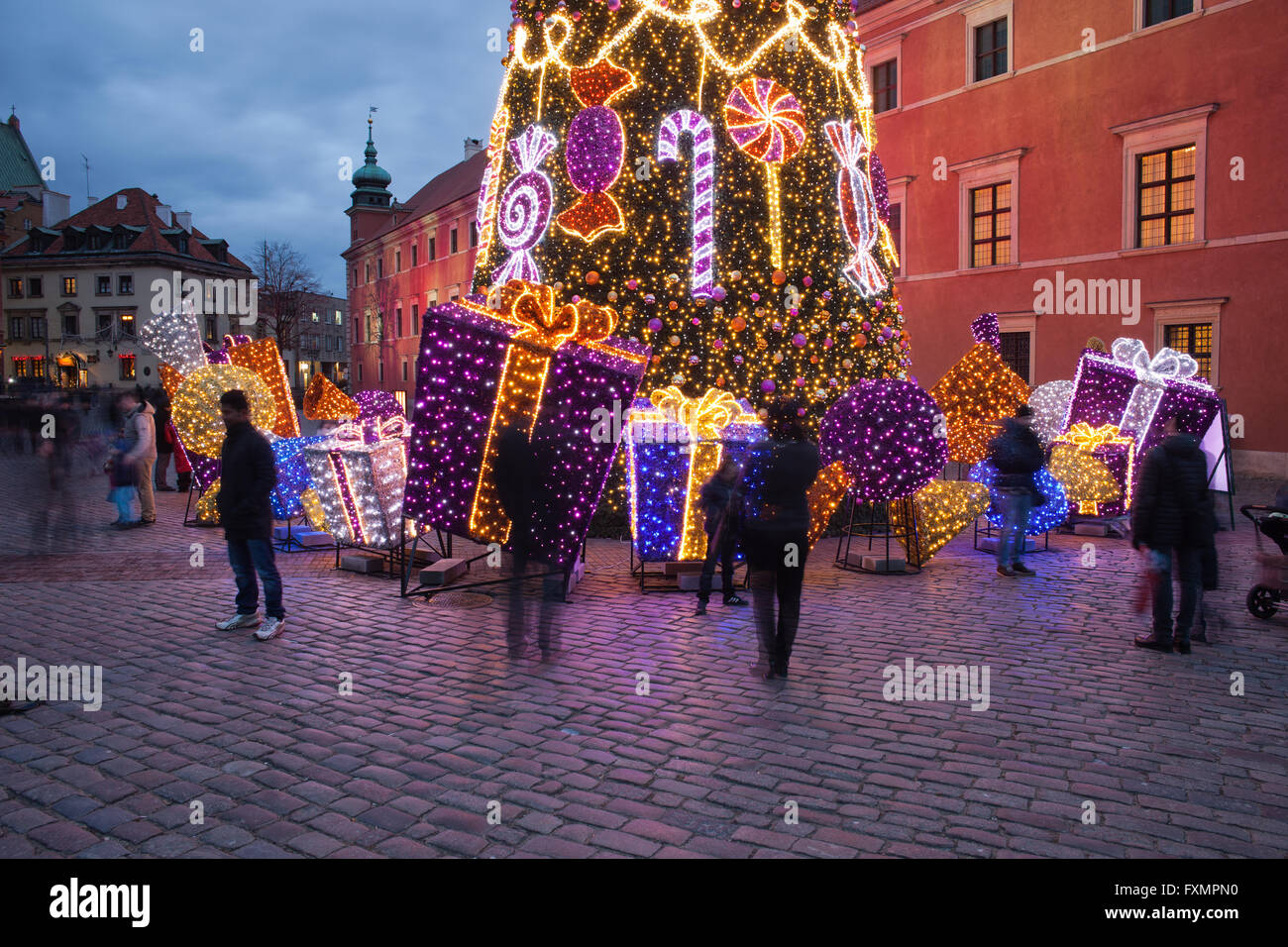 Poland, city of Warsaw, Old Town Square, Christmas Tree next to Royal Castle with gifts, presents, ornaments, evening - Stock Image