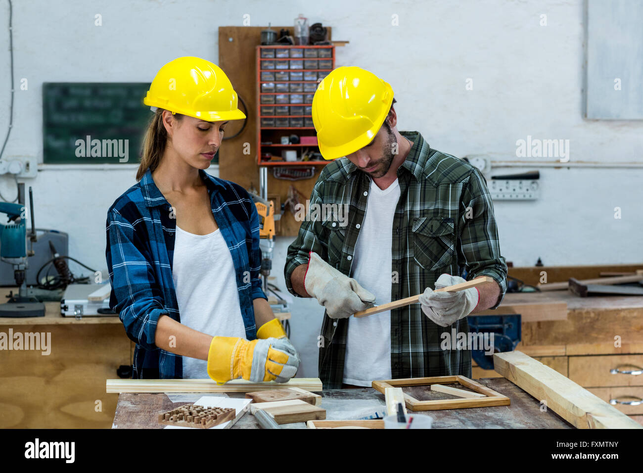 Male and female carpenters marking on wooden plank with pencil - Stock Image