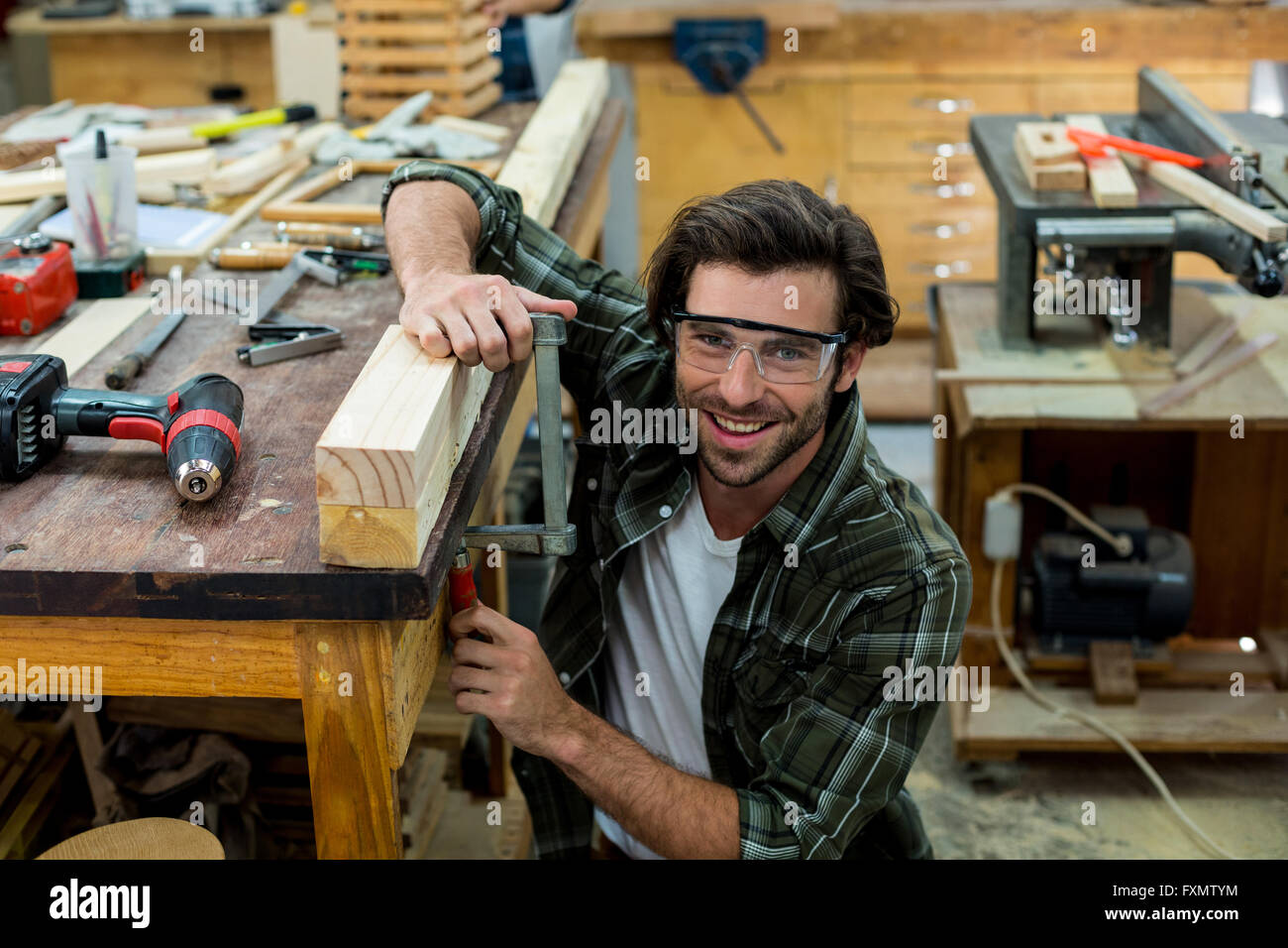 Portrait of male carpenter clamping wood - Stock Image
