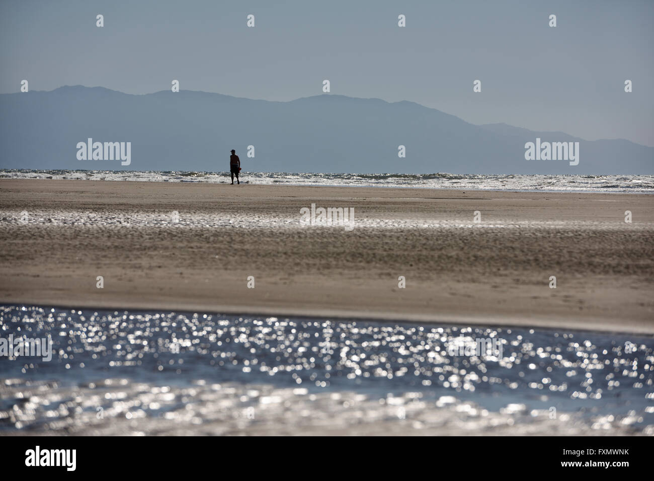 Man walking on beach at Nuevo Vallarta Mexico with Pacific ocean and Sierra Madre Mountains - Stock Image