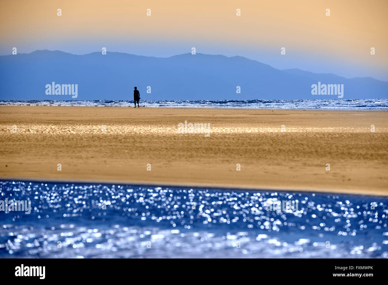 Single man on Mexican beach with colorful Pacific ocean and Sierra Madre Mountains Nuevo Vallarta Mexico blue and - Stock Image