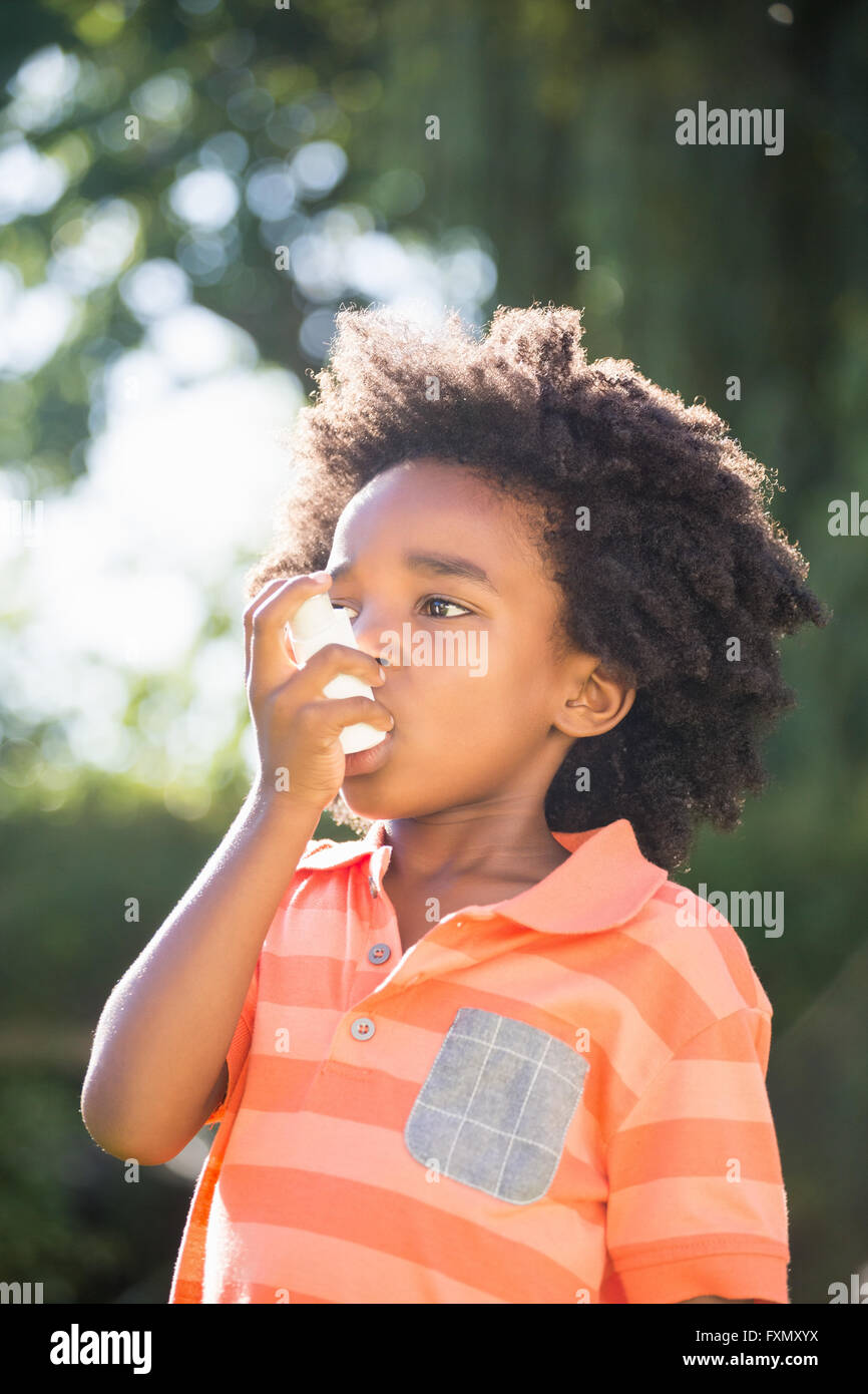 Cute mixed-race boy using a asthmatic spray - Stock Image
