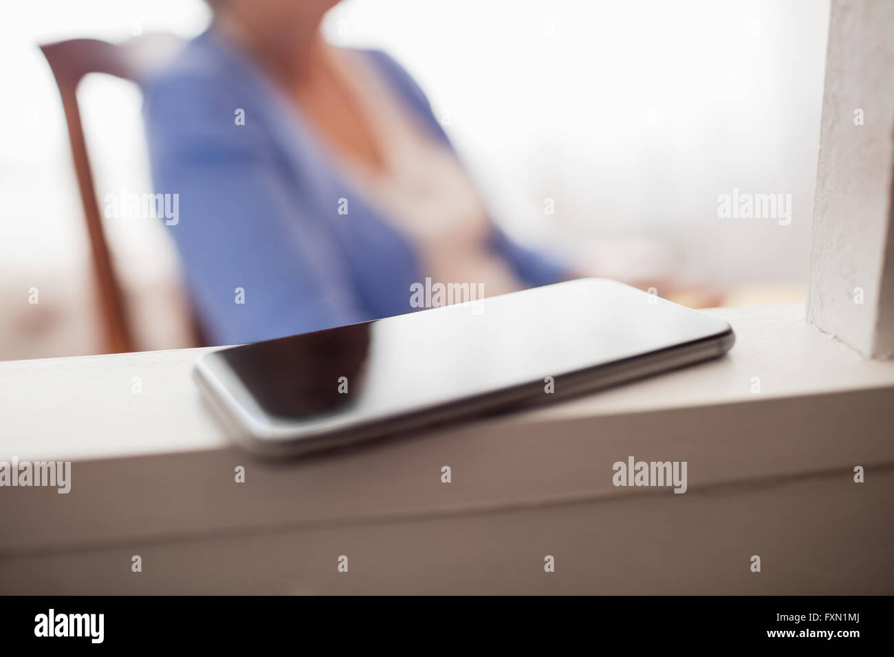 Smartphone with senior woman in rocking chair - Stock Image