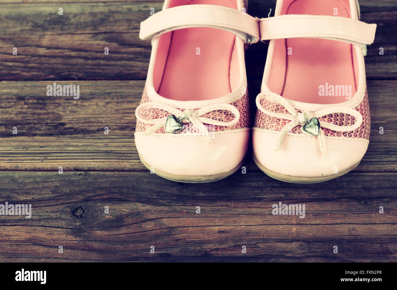 girl shoes over wooden deck floor. filtered image. - Stock Image