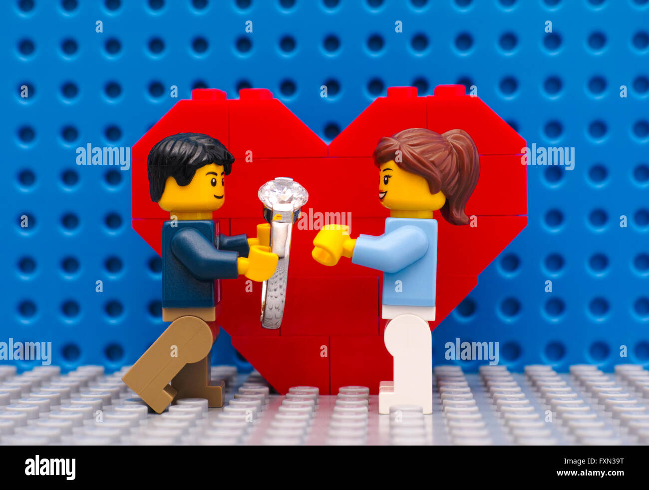 Lego man with ring makes marriage proposal to his girl standing in front of heart on Lego gray baseplate. - Stock Image