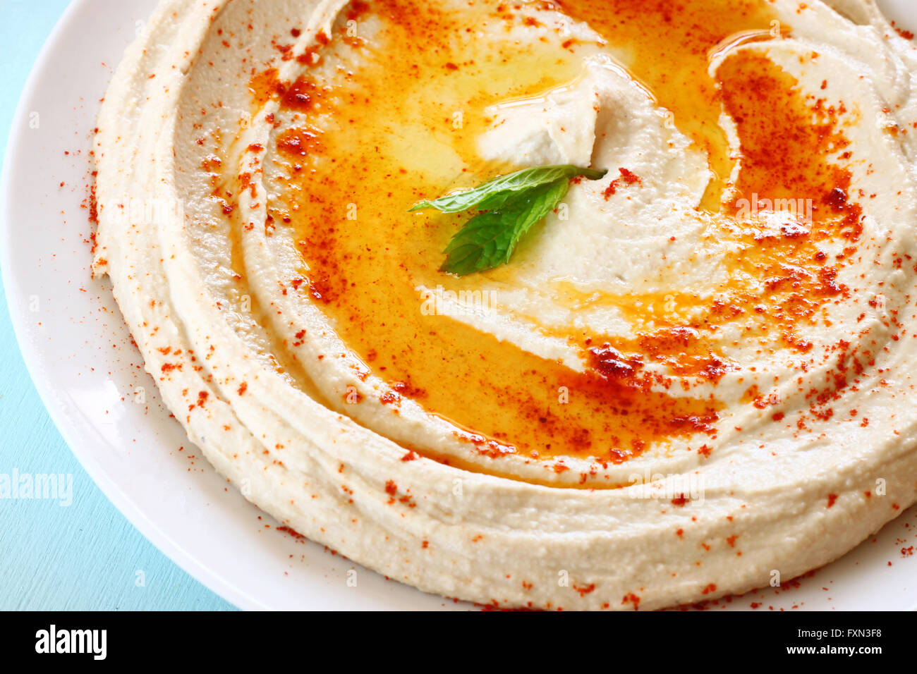hummus dip plate on wooden table - Stock Image