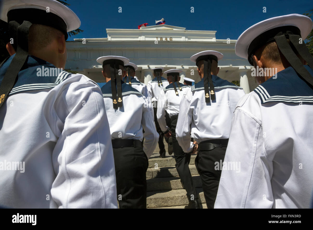 Black Sea Fleet sailors go to columned entrance to the Grafs Promenade on the Sevastopol waterfront, Crimea Republic - Stock Image