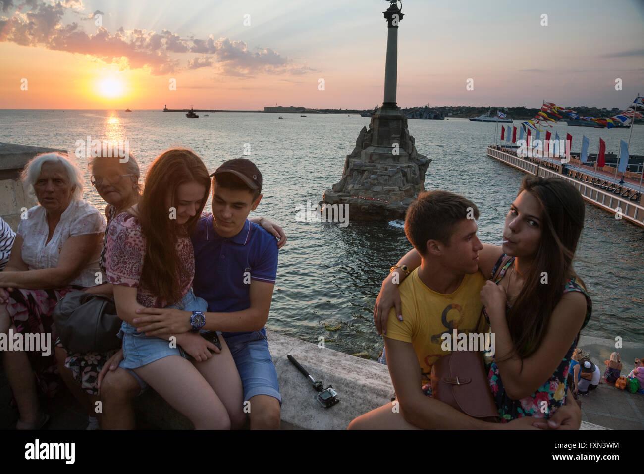 People enjoying at sunset near the Sunken Ships memorial, iconic monument and landmark in Sevastopol, Crimea Republic - Stock Image