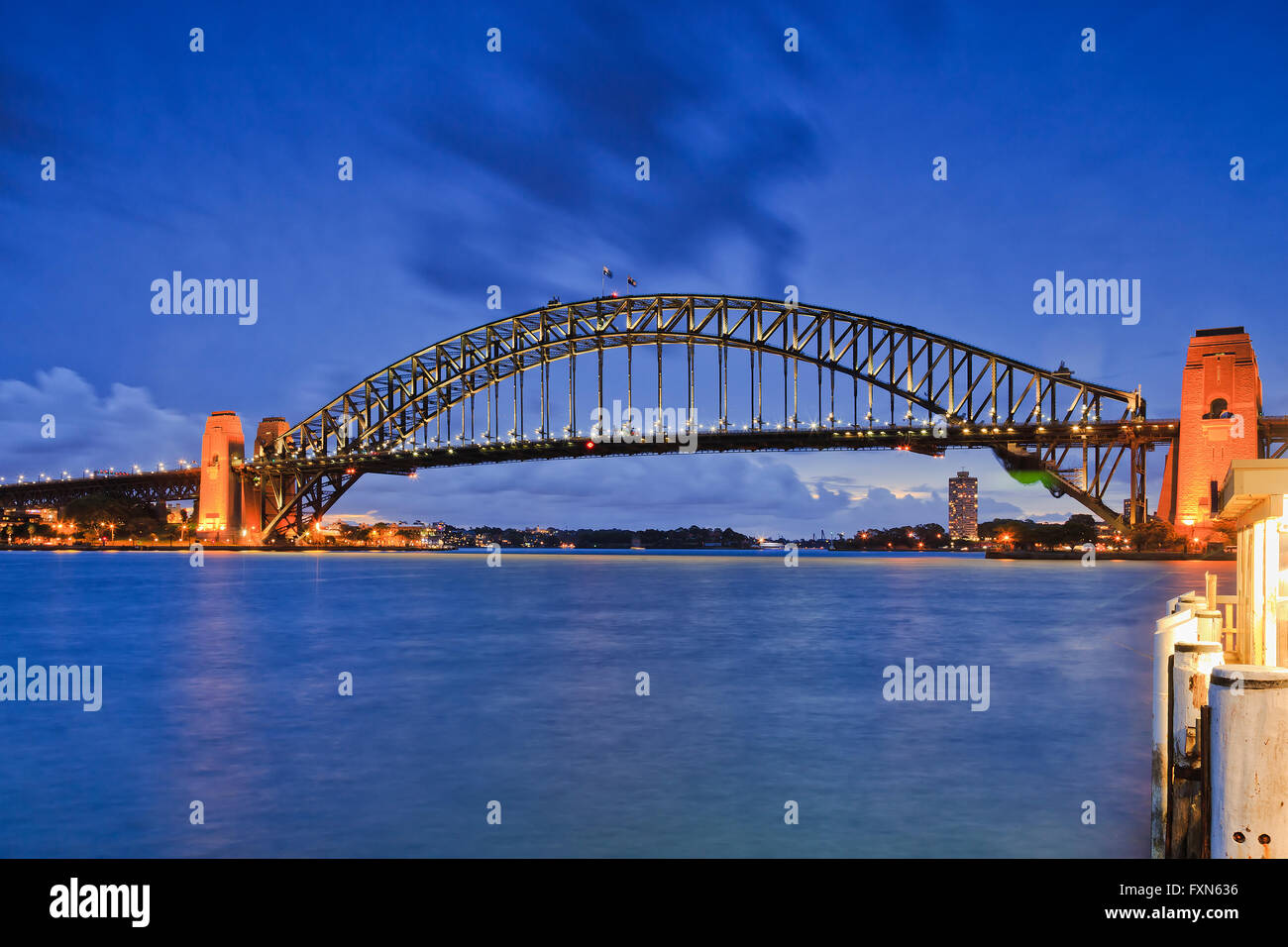 Side view of Sydney Harbour bridge against blue water and sunsettign sky with full illumination of metal arch and - Stock Image