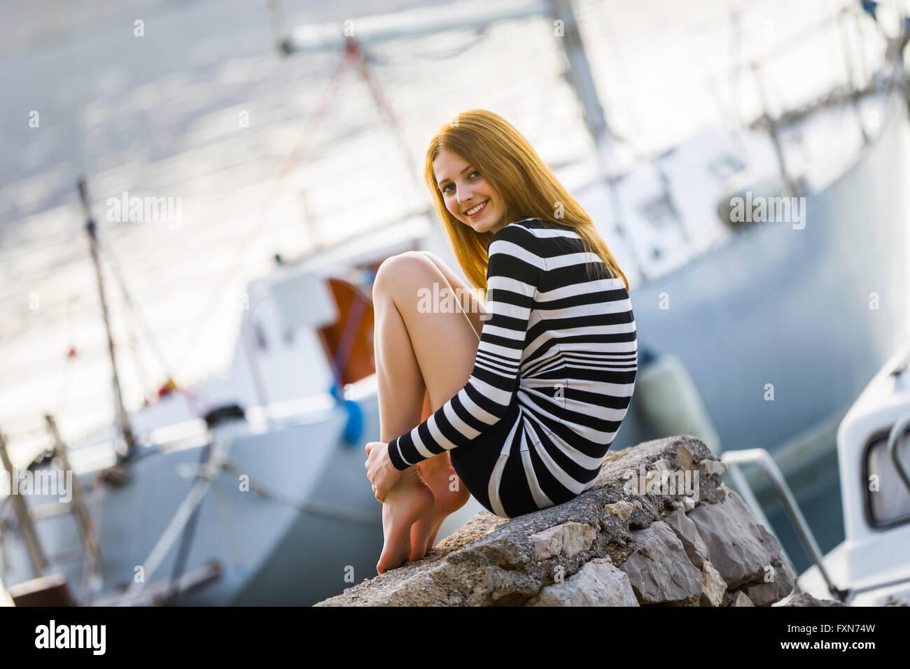 Cute teen girl teengirl posing before yacht in marina tucked legs barefeet bare-feet smiling angled photo outdoors Stock Photo