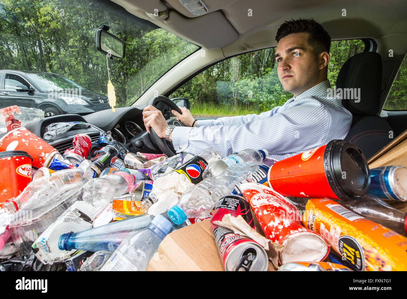 Car full of litter to show how much litter is thrown away each year on our roadsides - Stock Image