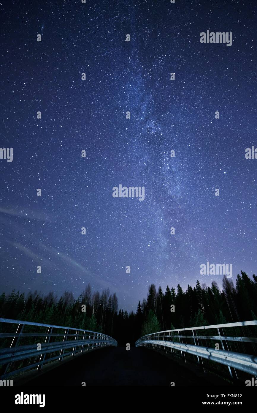 A night sky full of stars and visible milky way with a bridge on foreground. Road leading to dark forest. - Stock Image