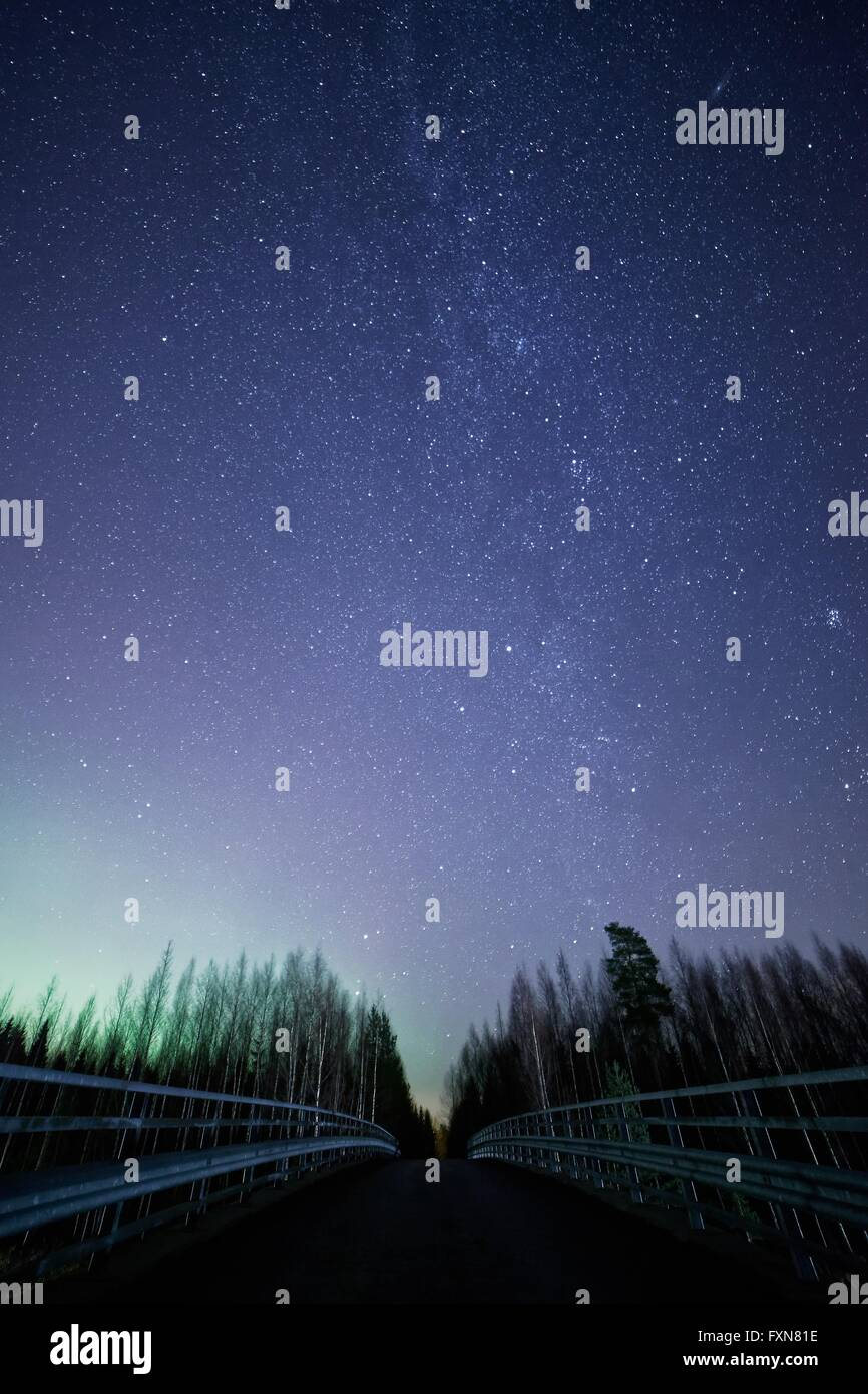 A night sky full of stars and visible milky way with a bridge on foreground. Green light of the northern lights - Stock Image