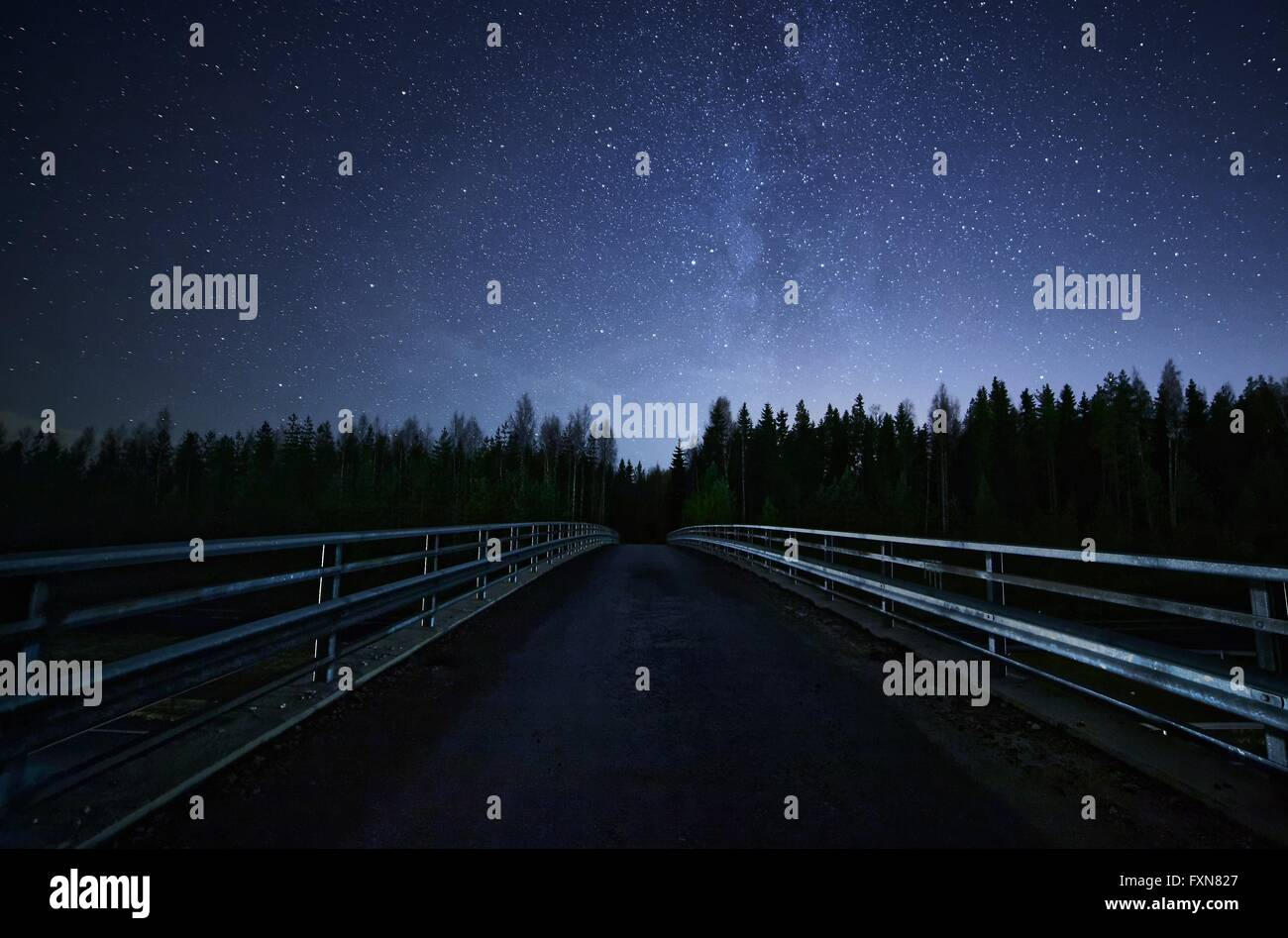 A road leading into night sky full of stars and visible milky way. A Bridge and dark forest on the foreground. - Stock Image