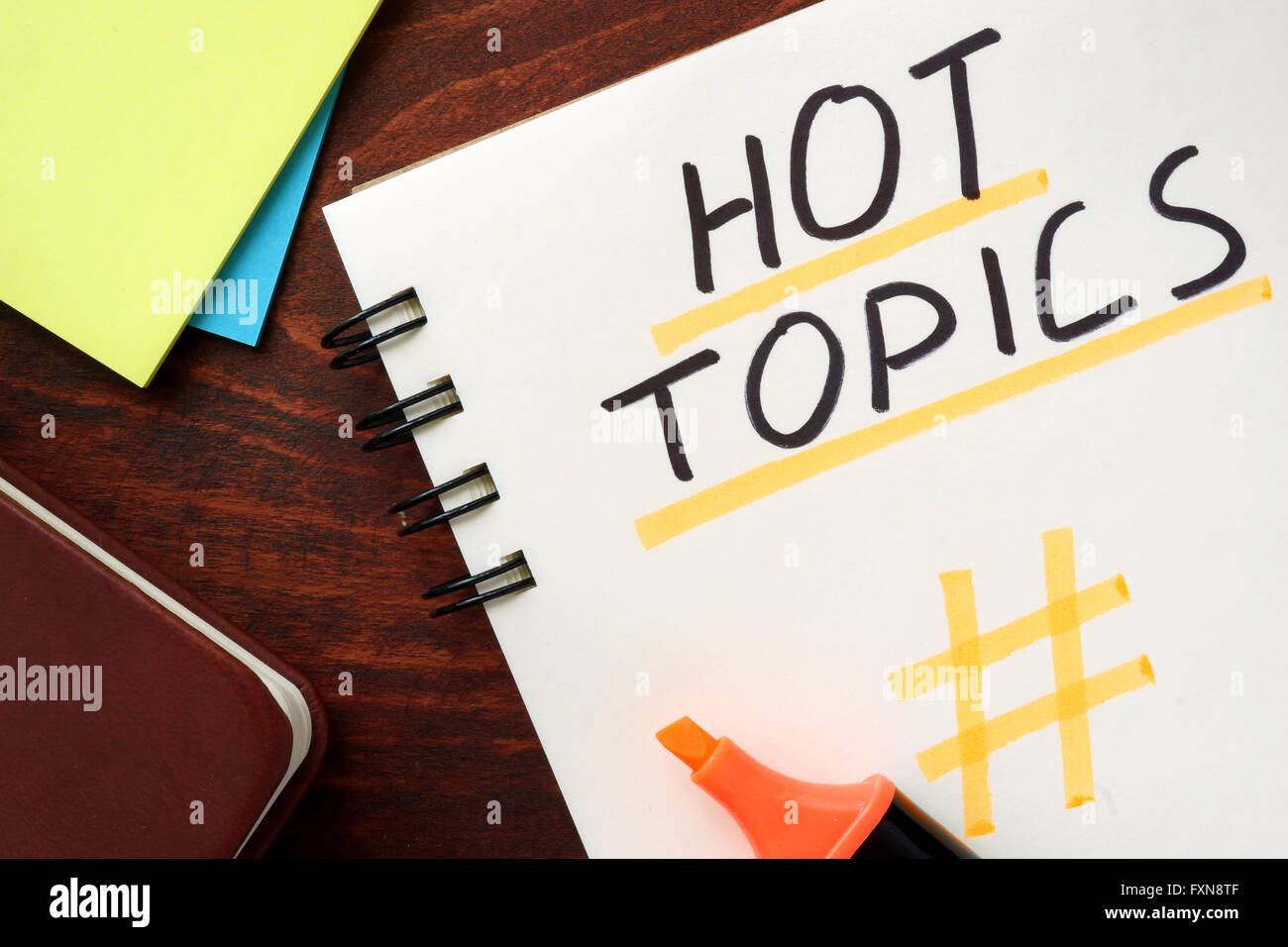 Hot Topics written in a notepad on a wooden background. - Stock Image