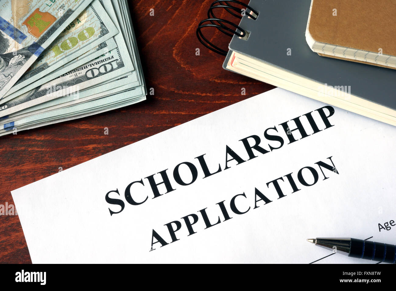Scholarship Application on a table and dollars. - Stock Image
