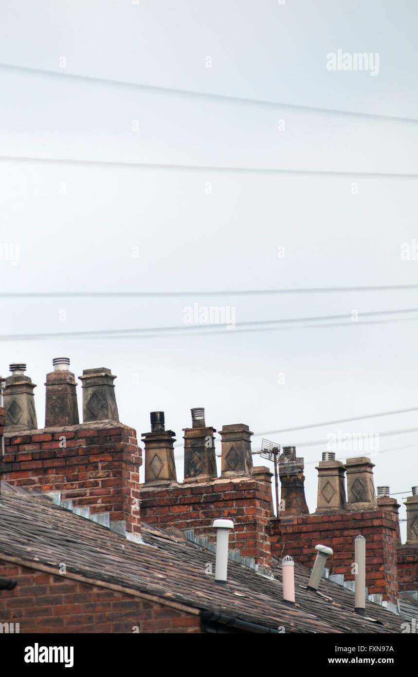 Rooftops and chimneys on a row of terraced houses in Stretford, Manchester, England, UK - Stock Image
