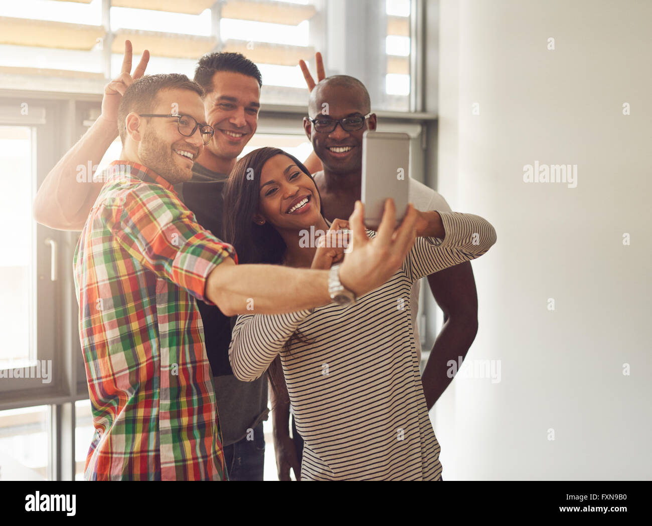 Diverse group of happy young workers taking pictures and making symbolic hand gestures for camera phone at small - Stock Image